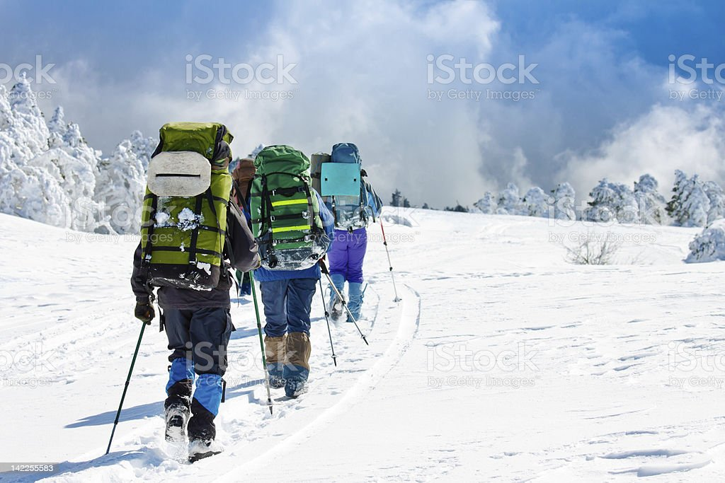 A group of people hiking up a snow covered mountain stock photo