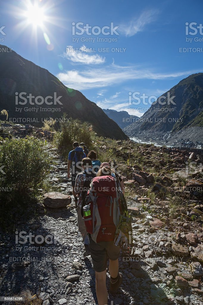 Group of People Hiking Up to Fox Glacier, New Zealand stock photo