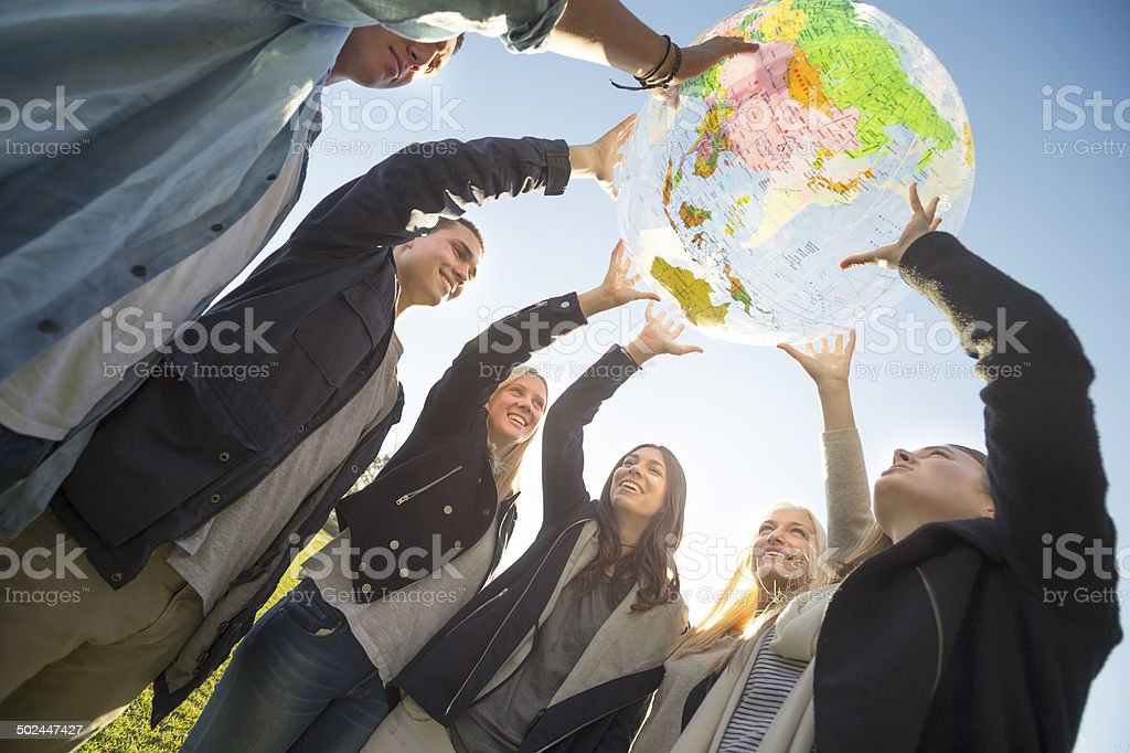 Group of people holding a world globe stock photo