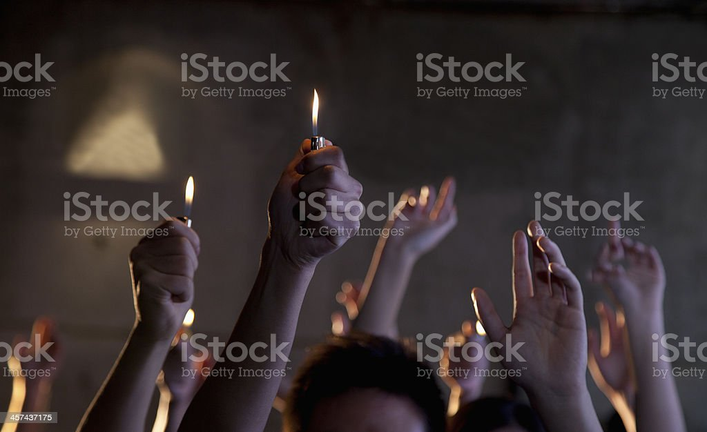 Group of people holding cigarette lighters at a concert stock photo