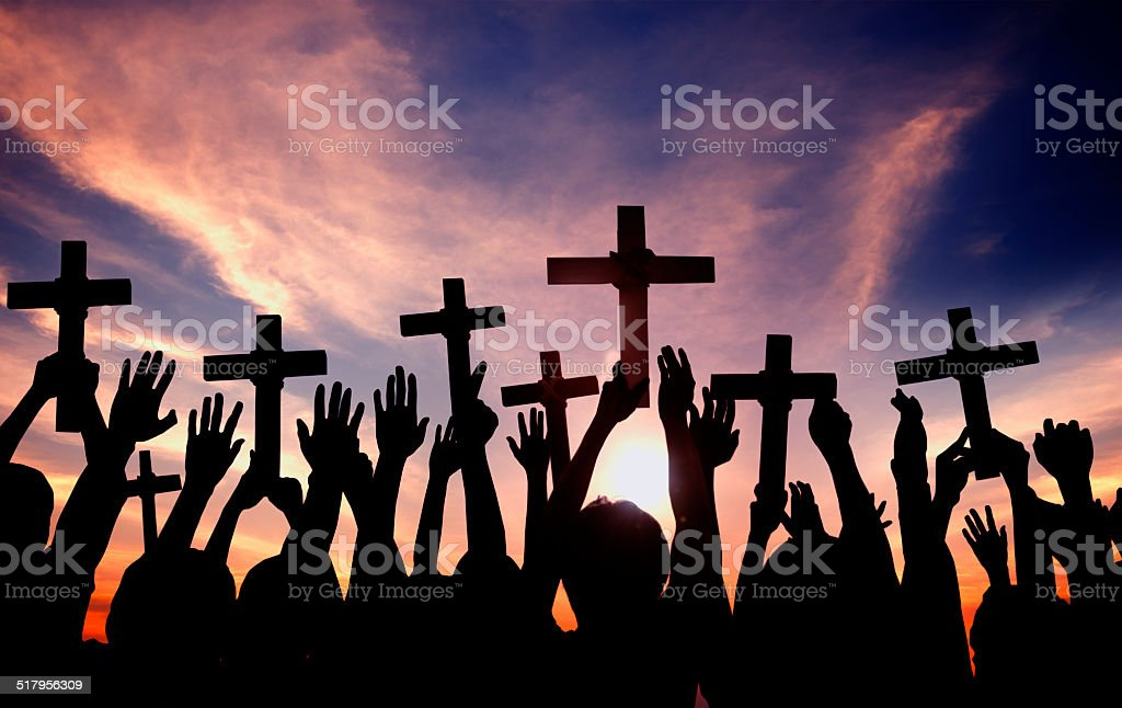 Group of People Holding Cross and Praying in Back Lit stock photo