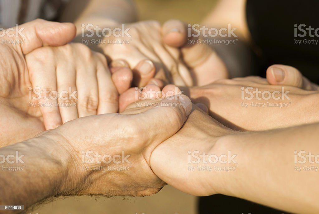 Group of people holding each others hands symbolizing a bond stock photo