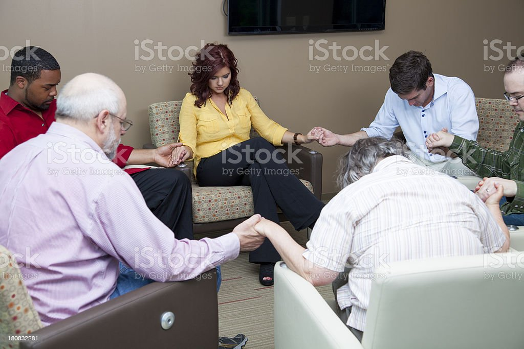 Group of people holding hands and praying royalty-free stock photo