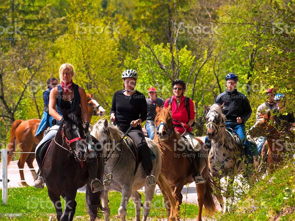 A group of people horse back riding stock photo