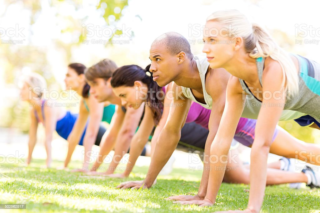 Group Of People In Bootcamp Workout Class Doing Pushups stock photo