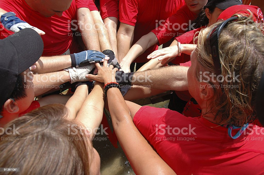 Group of people in red shirts holding their hands together royalty-free stock photo