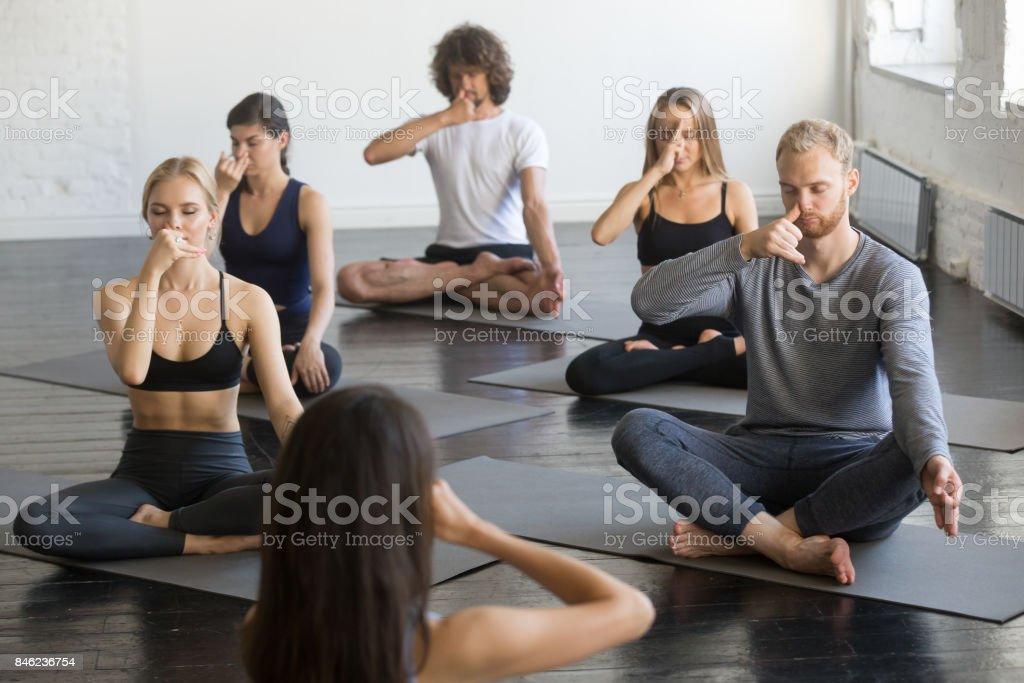 Group of people in Sukhasana pose making nadi shodhana pranayama stock photo
