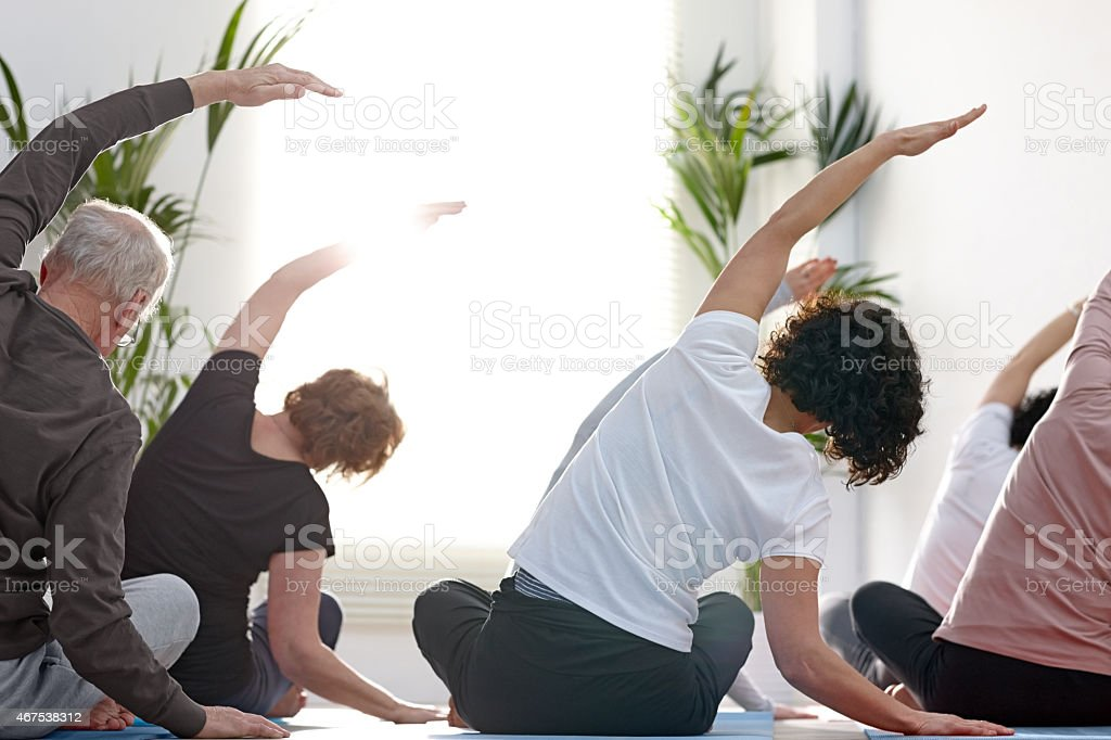 Rear view of group of people in the gym center doing stretching...