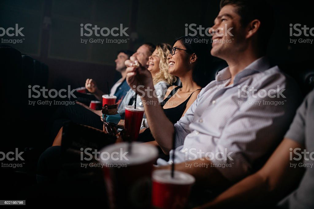 Group of people in theater with popcorn and drinks stock photo