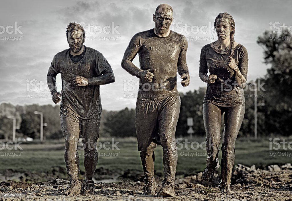group of people jogging in mud stock photo