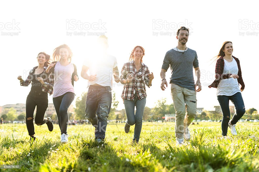 Group of people jumping on the park at dusk stock photo