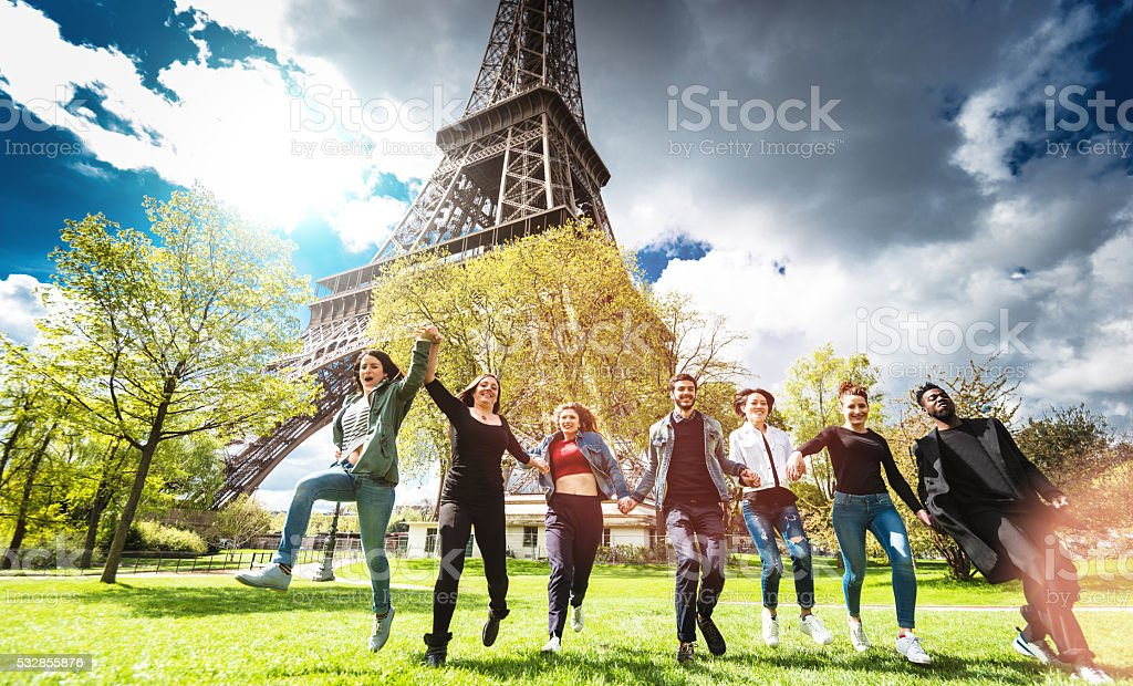 Group of people jumping on the park under tour eiffel stock photo