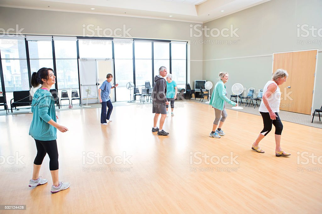 Diverse group of people take a line dancing class at local recreation...