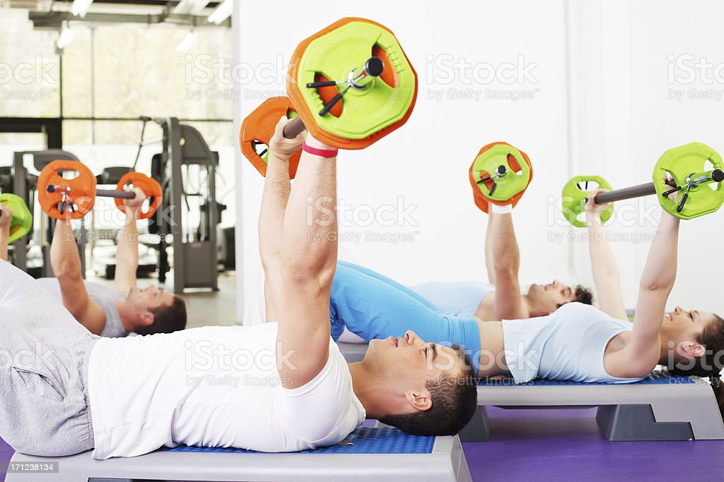 Group of people lifting barbells in weight training class. royalty-free stock photo