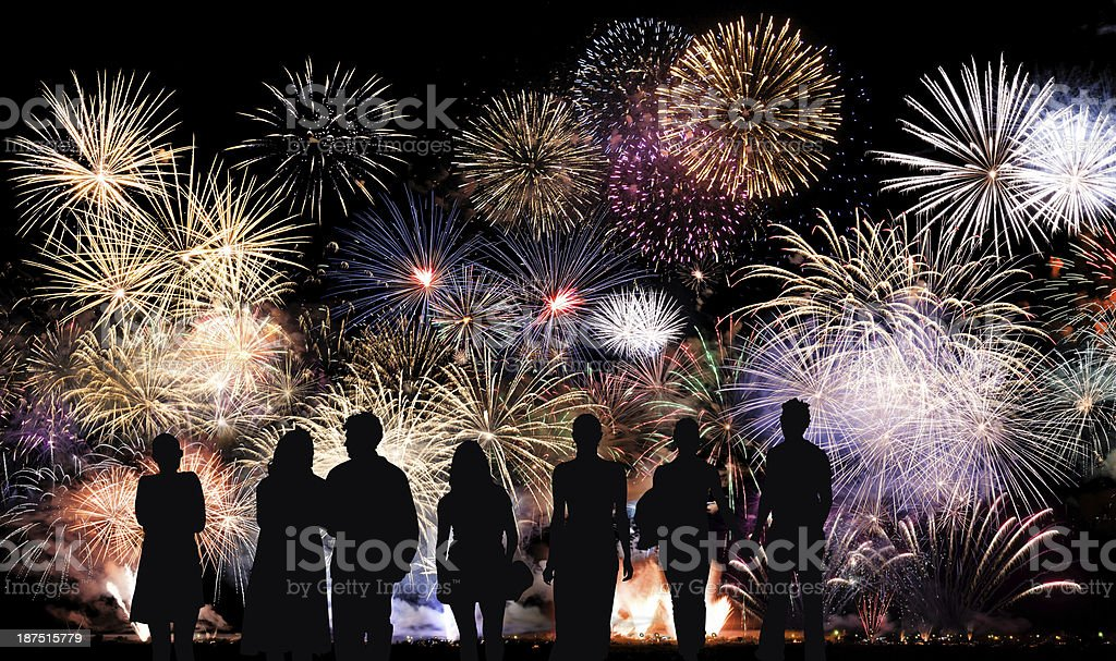 Group of people look at colorful holiday fireworks stock photo