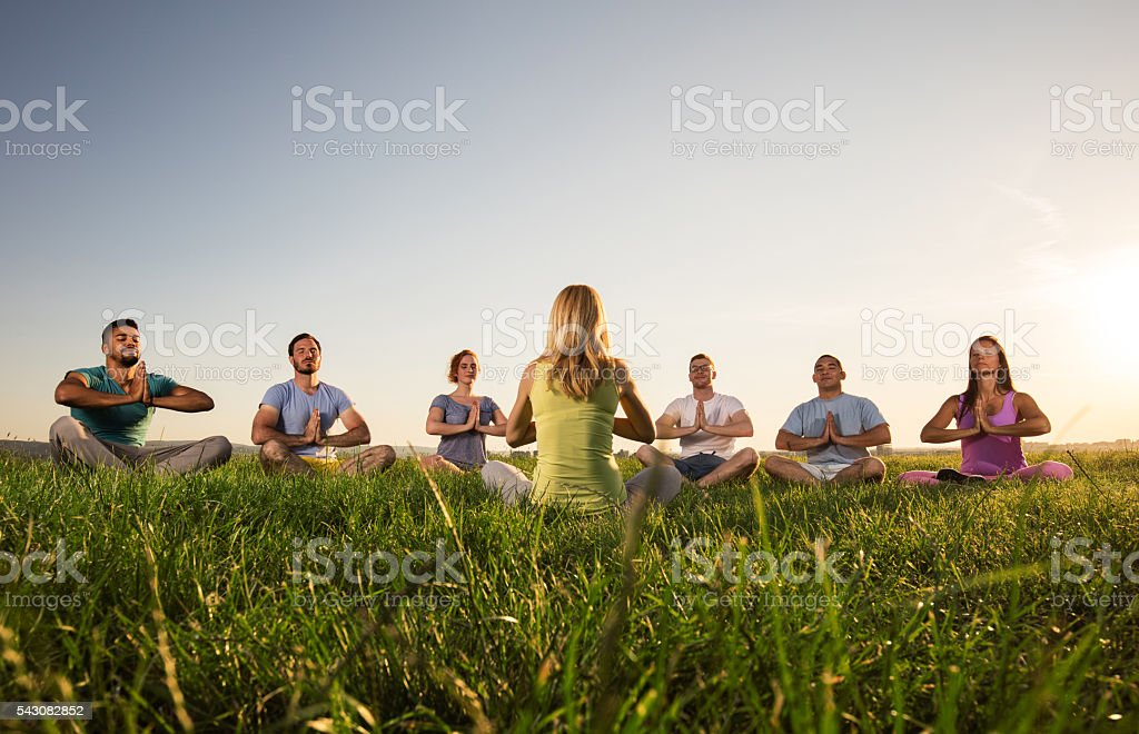 Group of people meditating during yoga class at sunset. stock photo