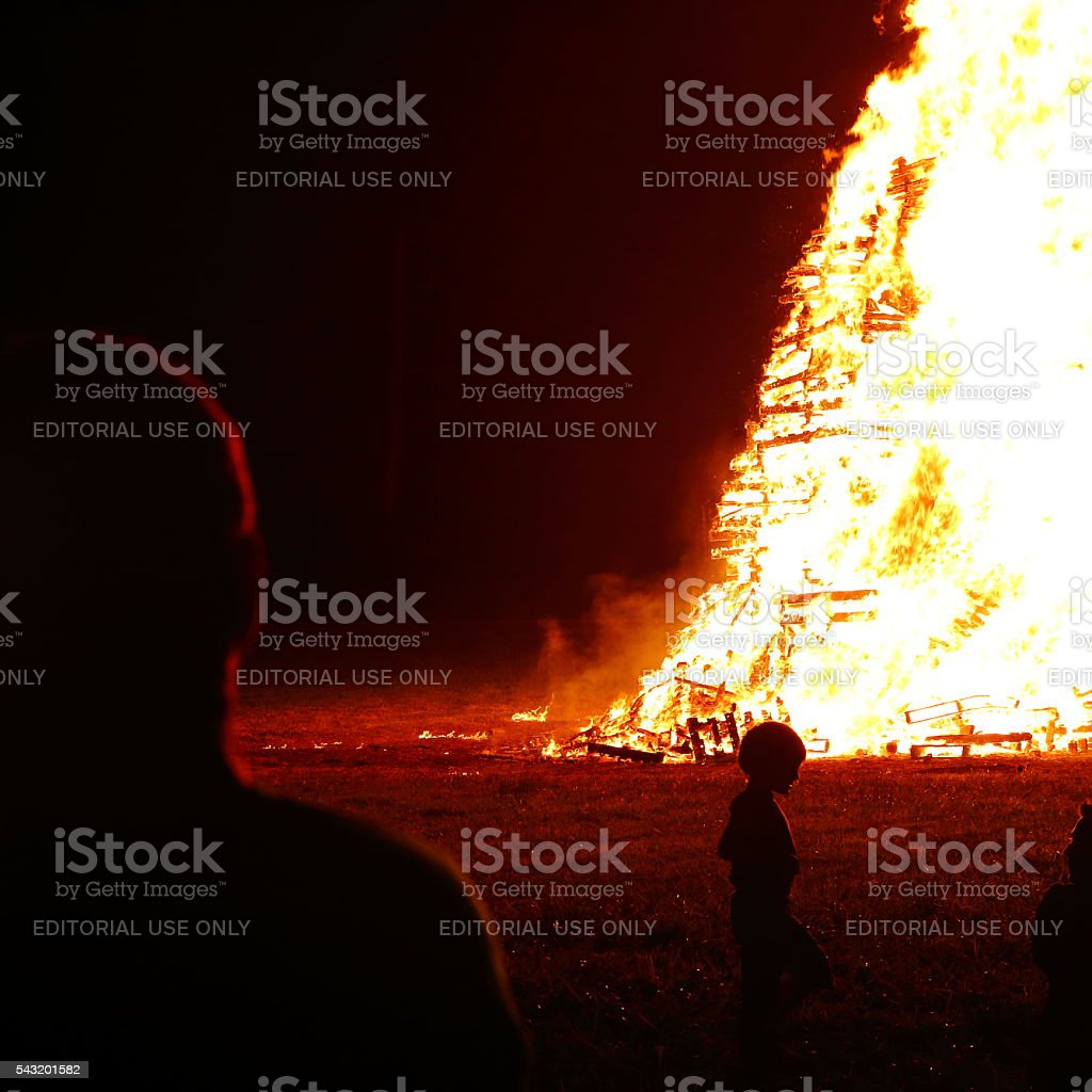 Group of people meeting around big bonfire in summer stock photo
