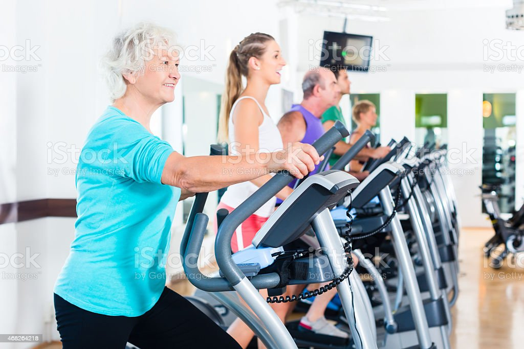 Group of people on elliptical trainer exercising in gym stock photo