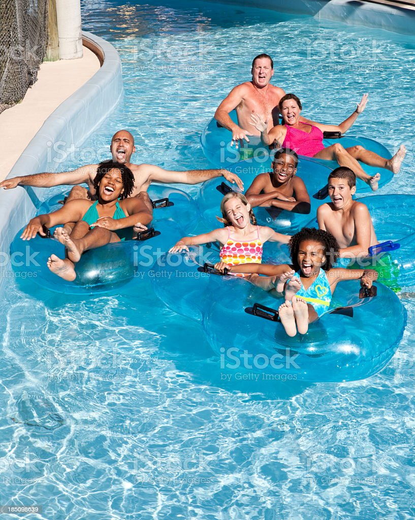 Group of people on innertubes at water park stock photo