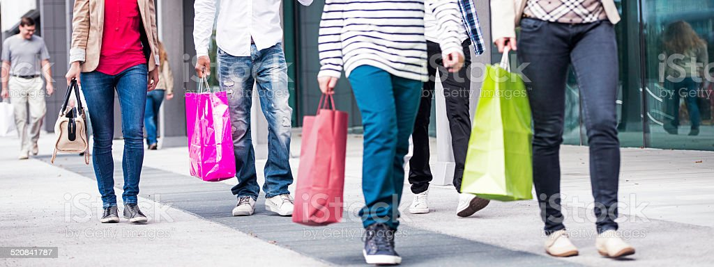 Group of People on Sidewalk with Shopping Bags stock photo