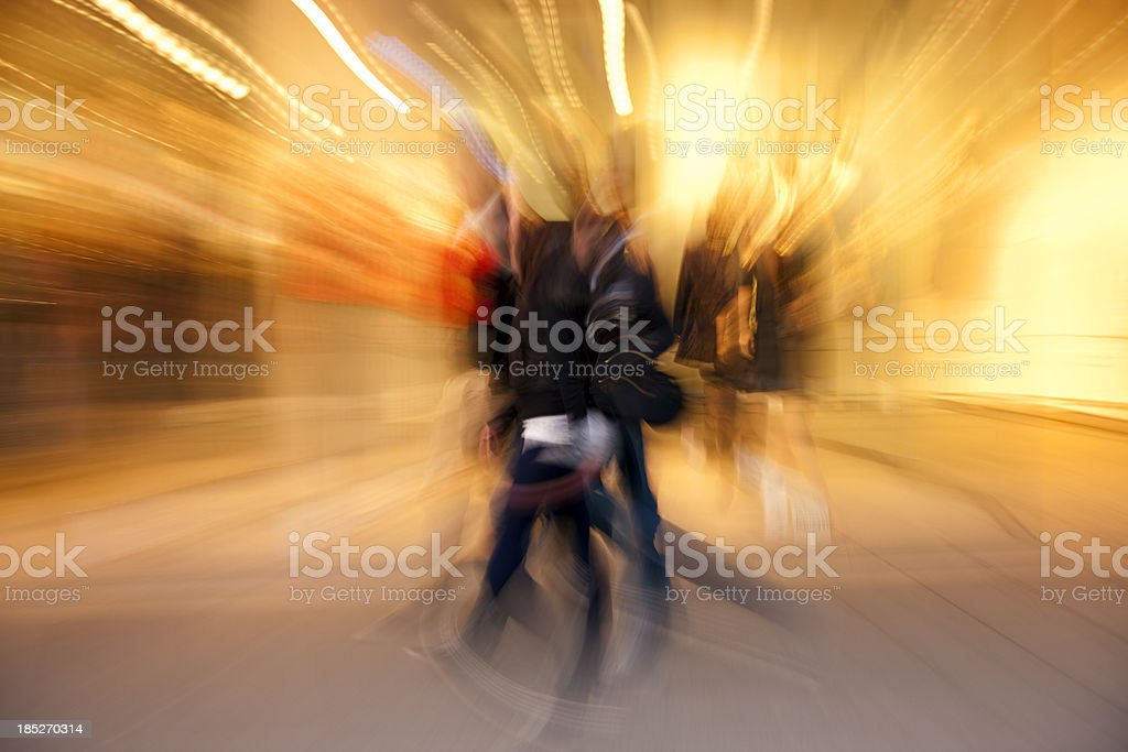 Group of People Passing Illuminated Clothing Store, Blurred Motion royalty-free stock photo