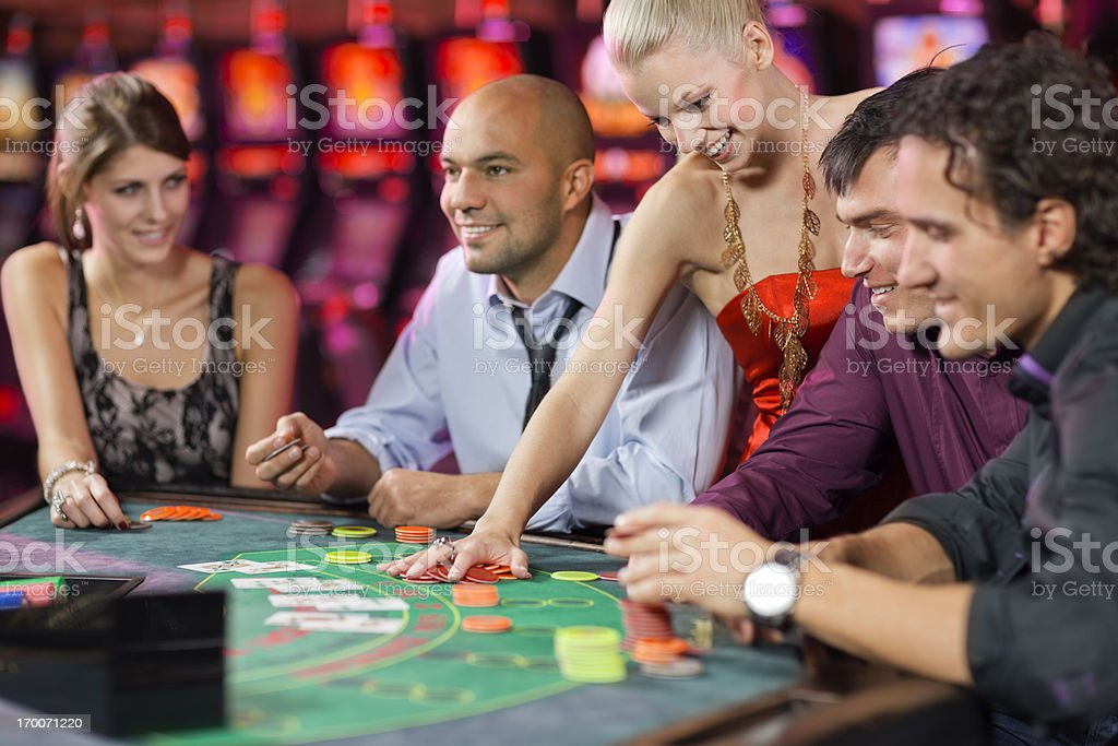 group of people playing blackjack in the casino stock photo