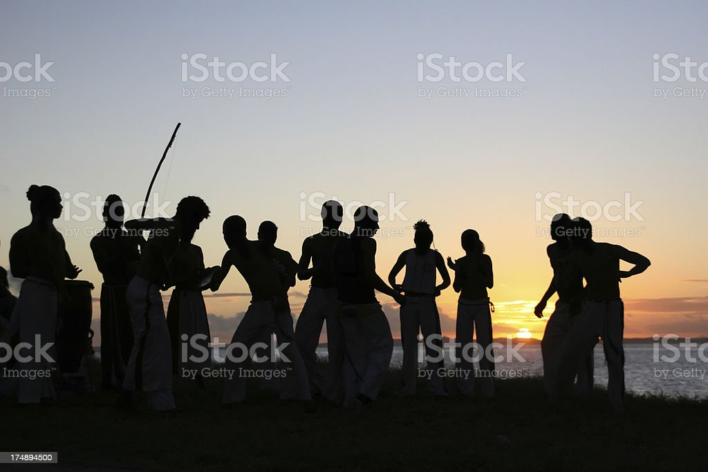 Group of people playing capoeira in the sunset stock photo