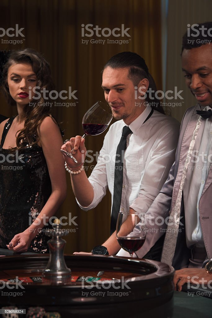 Group of people playing roulette at casino stock photo