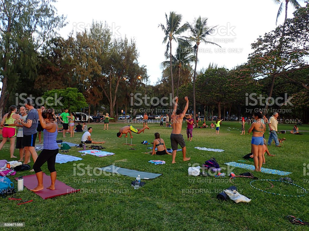 Group of people practice AcroYoga, handstands, and hula-hooping stock photo
