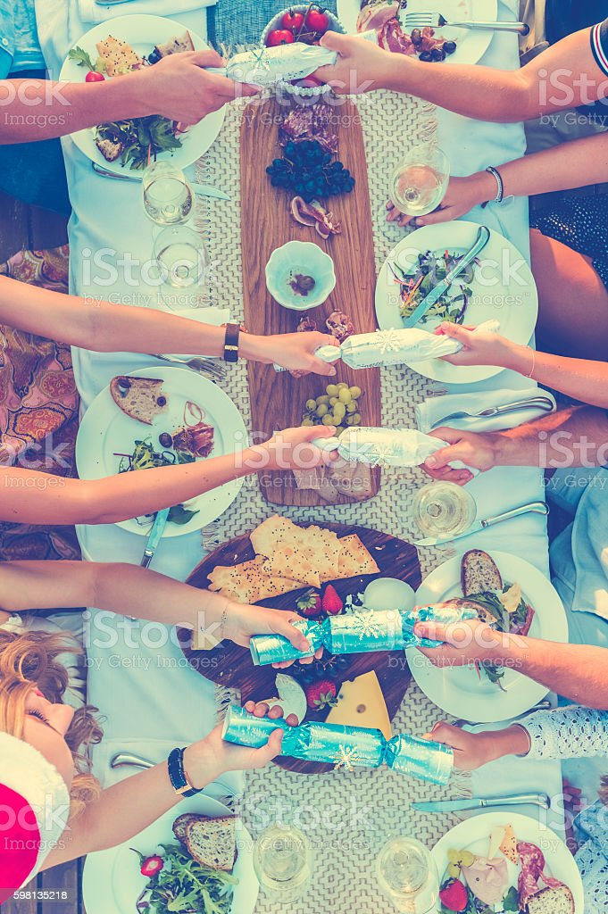 Group of people pulling Christmas crackers. stock photo