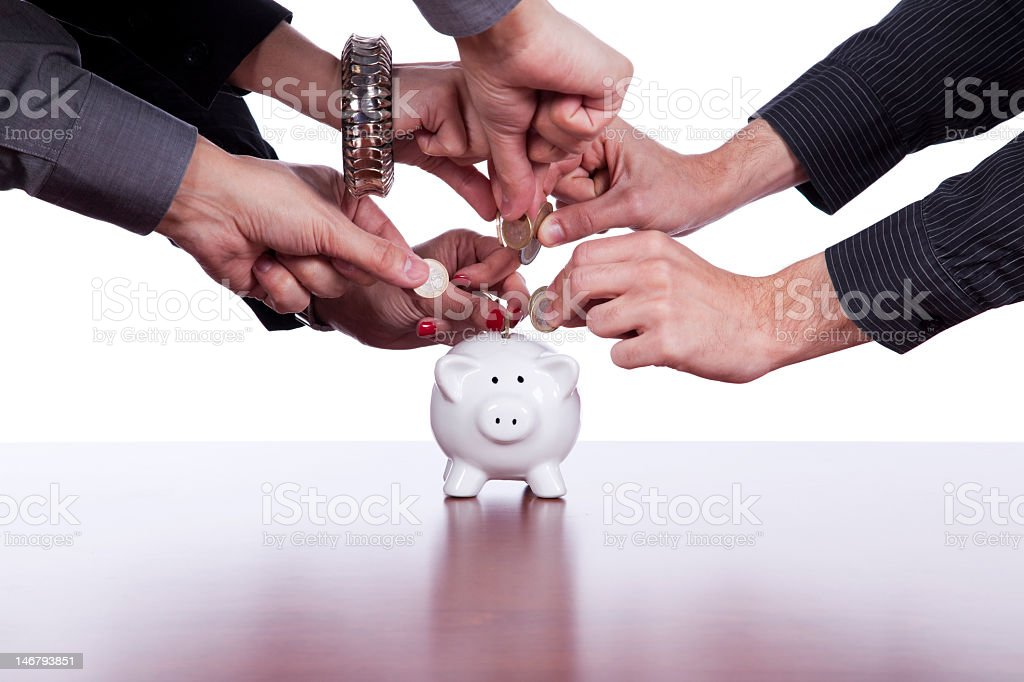 A group of people putting coins in to a piggybank royalty-free stock photo