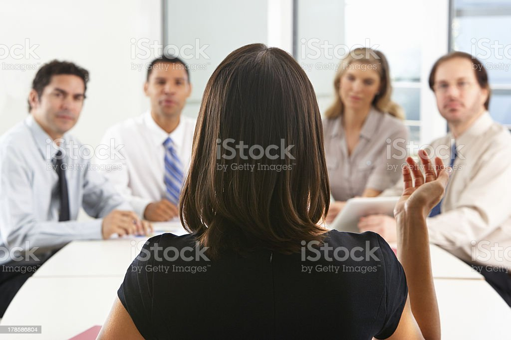 Group of people seated around boardroom table stock photo