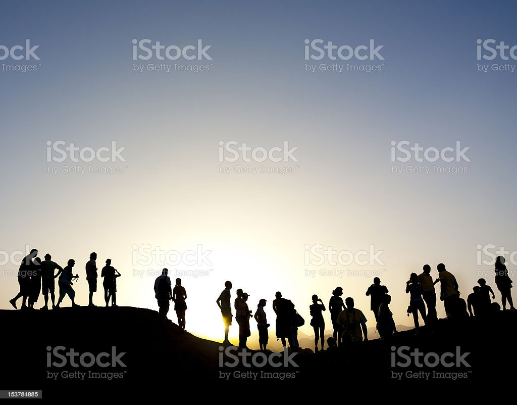 Group of people silhouetted against the sun stock photo