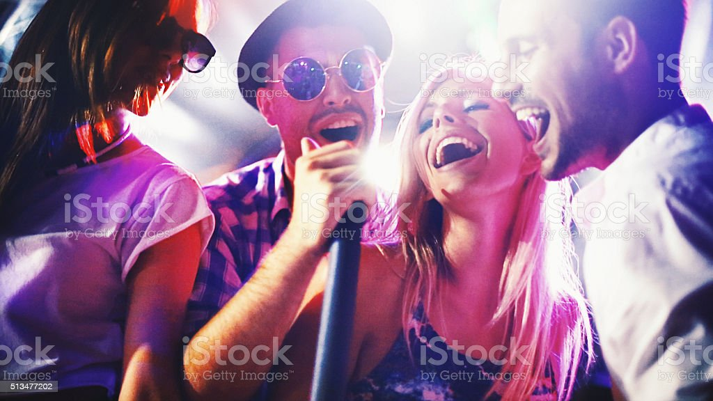 Group of people singing karaoke. stock photo