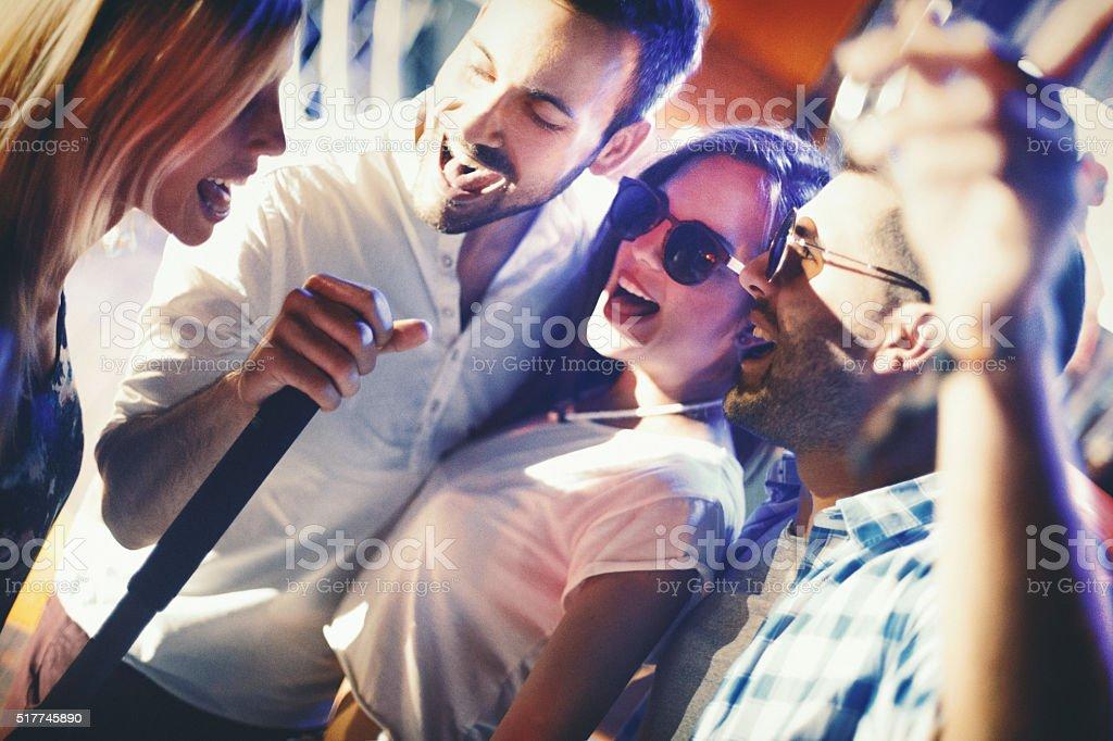 Group of people singing karaoke. stock photo