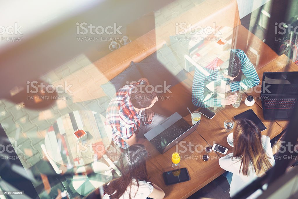 Group of people sitting at a cafe, talking and enjoying stock photo