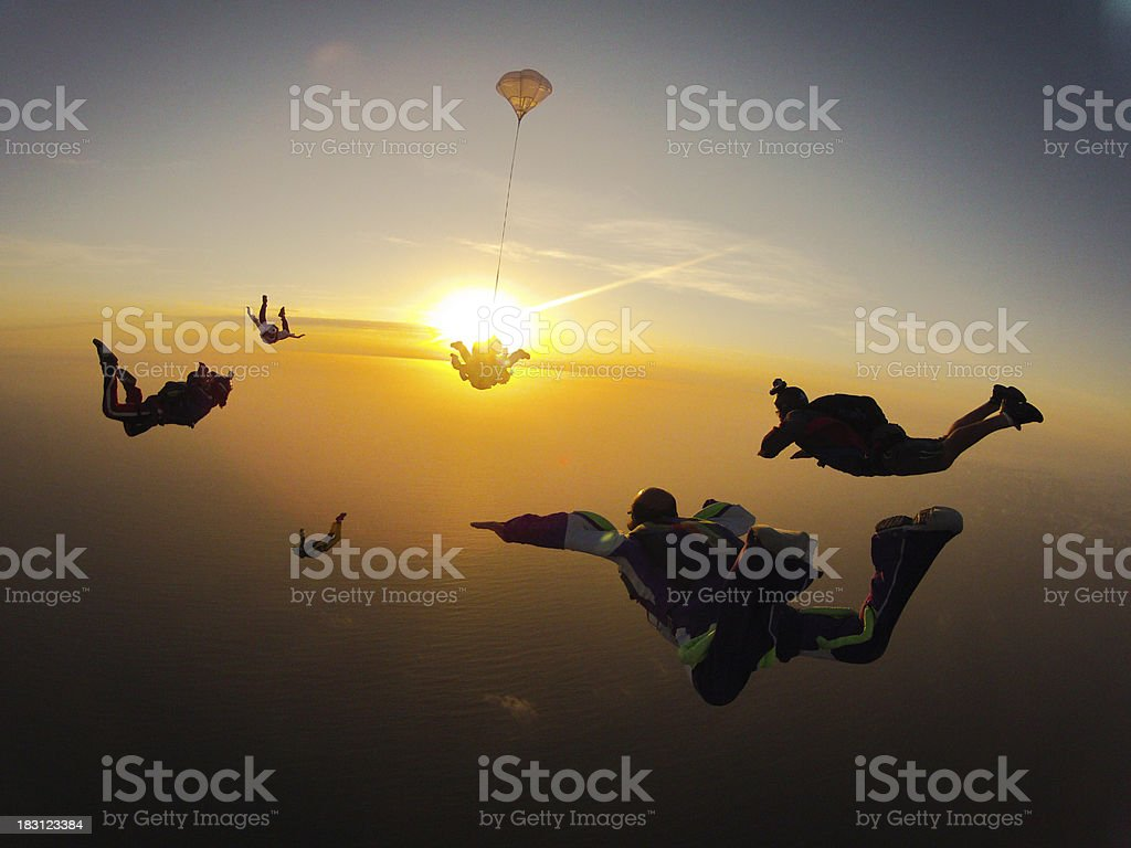 Group of people skydiving at sunset stock photo
