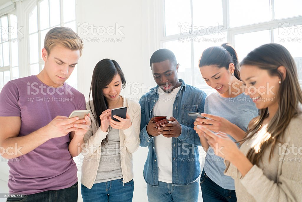 Group of people social networking on their phones stock photo