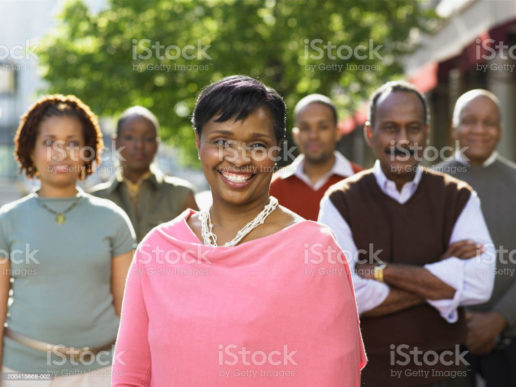Group of people standing on sidewalk, mature woman in foreground royalty-free stock photo