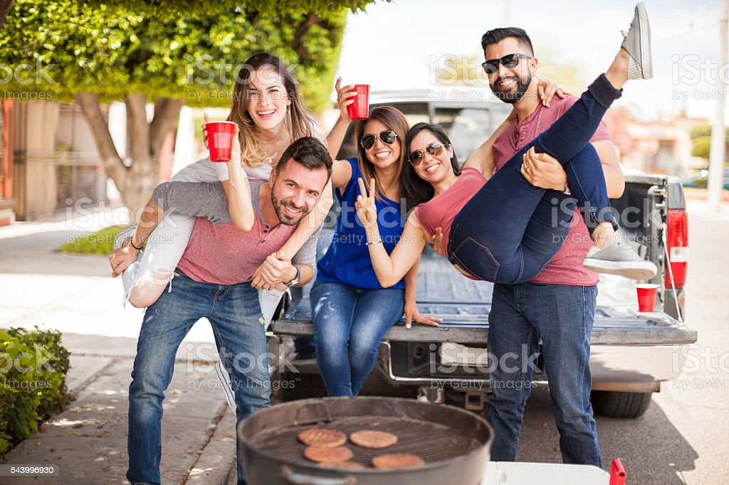 Group of people tailgating and grilling burgers stock photo