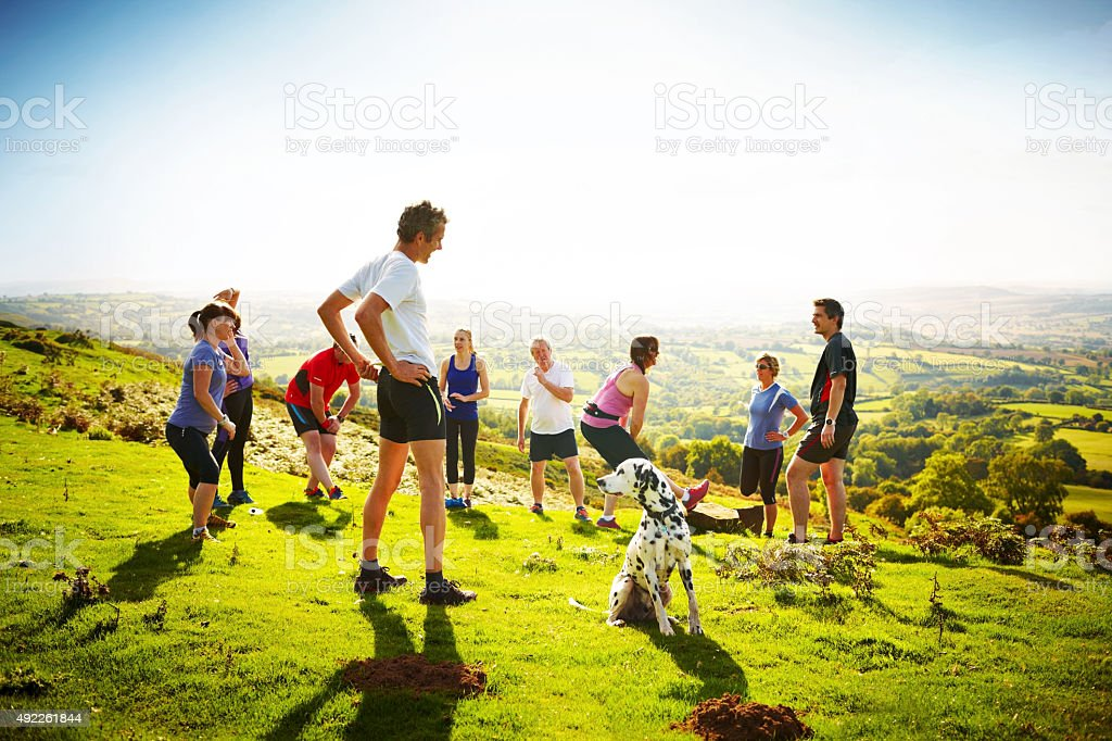 Group of people taking a break from running on mountain stock photo