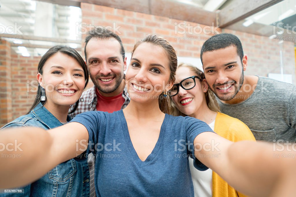 Group of people taking a selfie at the office stock photo