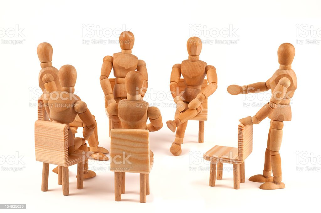 group of people talking about - wooden mannequins in circle stock photo
