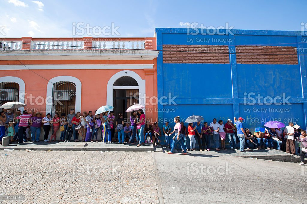 Group of people waiting in line at a public supermarket stock photo