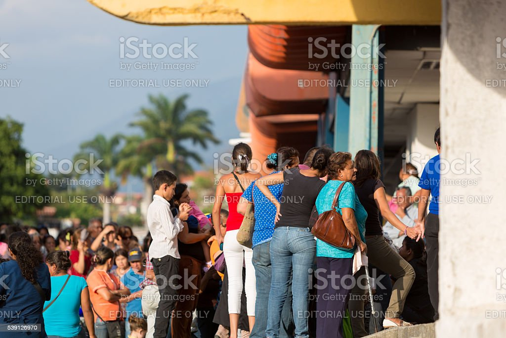 Group of people waiting in line at public supermarket, Venezuela stock photo