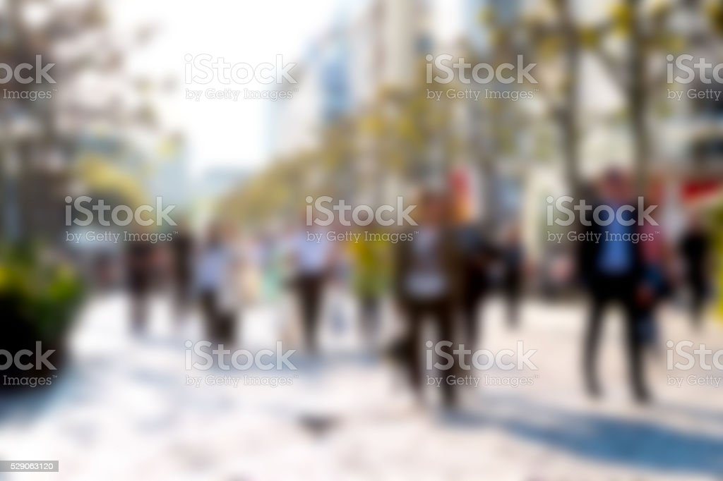 Group of people walking by a shopping street. stock photo