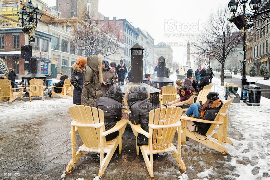 Group of people warming up around public fireplace Old Montreal stock photo