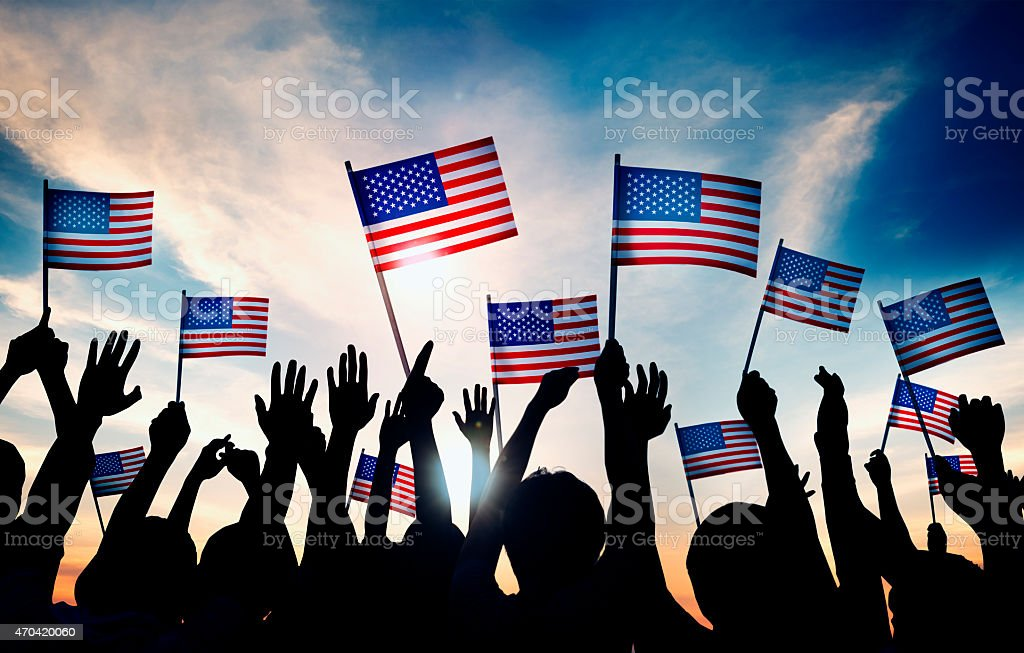 Group of People Waving American Flags in Back Lit stock photo