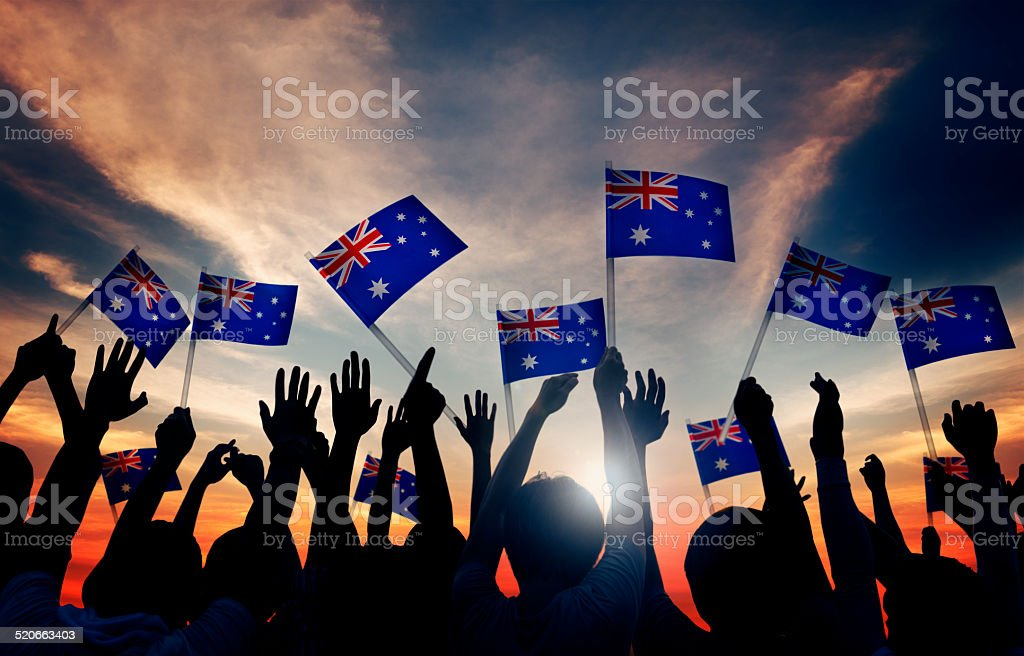 Group of People Waving Australian Flags in Back Lit stock photo