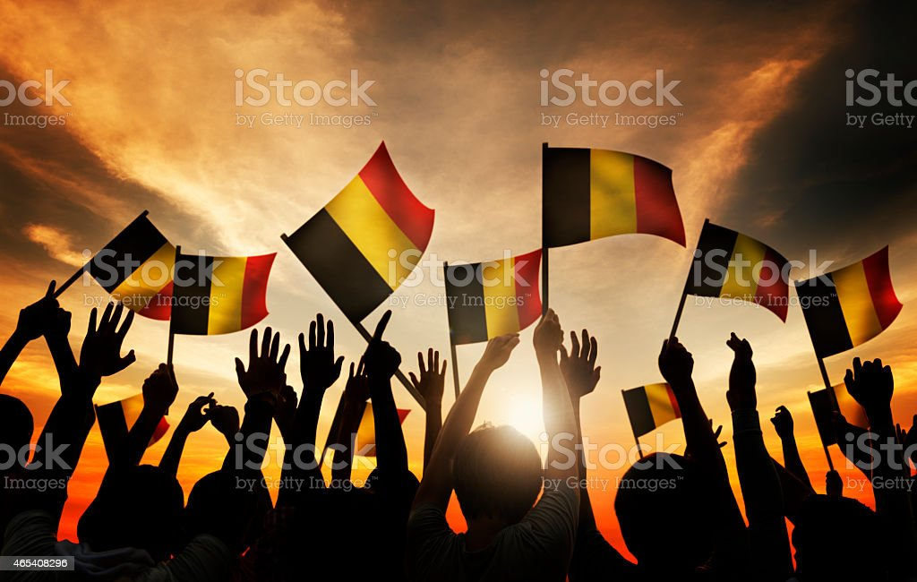 Group of People Waving Belgian Flags in Back Lit stock photo